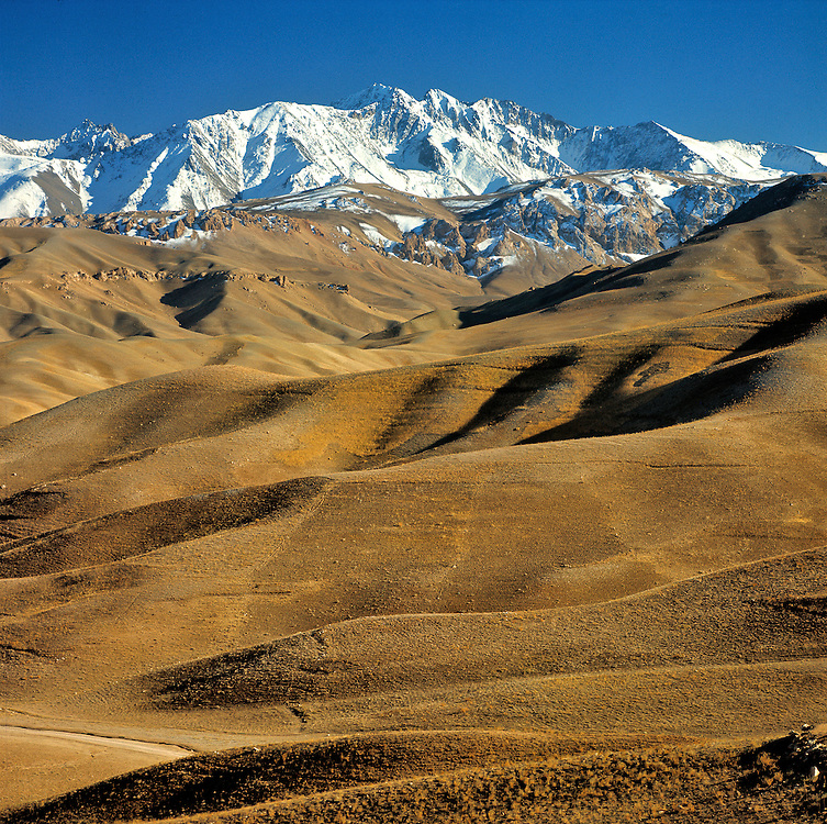 Rolling hills lead to the snow fields of the rugged Hindu Kush Mountains near Bamian Valley, Afghanistan.