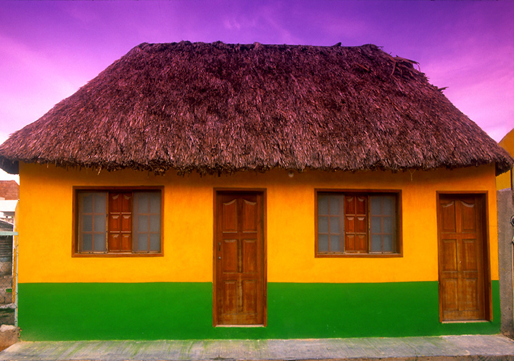 Colorful house with traditional palapa roof on Isla de Holbox, Mexico.