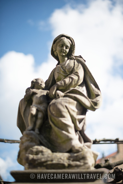 A stone statue of Madonna and Child outside the entrance to the Church of Our Lady, Bruges, Belgium.