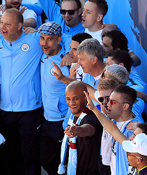 Manchester City manager Pep Guardiola (flat cap top) and Vincent Kompany (centre) on stage during the trophy parade in Manchester.