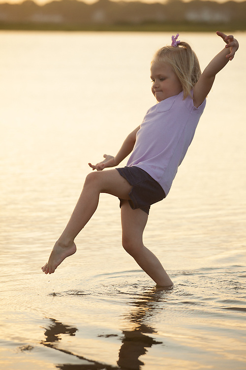 Photo of a girl tiptoeing through a tidal pool in Dennis on Cape Cod