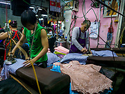 23 FEBRUARY 2018 - BANGKOK, THAILAND: Workers press clothes in one of the few shops still open in Pratunam Market. Pratunam Market was one of the largest clothing markets in Bangkok. New airconditioned markets, like Platinum and Palladium malls opened nearby, siphoning away customers. Now there are only a handful of merchants left in the market and Bangkok city officials have plans to shut the market and redevelop the land.     PHOTO BY JACK KURTZ