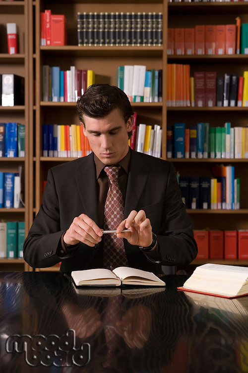 Man wearing suit holding pen over book at desk in library