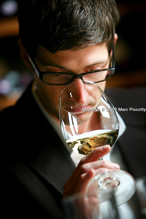 SHOT 1/13/09 12:02:39 PM - Ryan C. Gaudin, the Wine Director at Mizuna and partner at Osteria Marco, studies the bouquet of a glass of white wine while blind tasting different wines at Barolo Grill in Denver, Co. one afternoon. Gaudin is studying to complete the third of four levels of the Advanced Level, Court of Master Sommeliers test. A sommelier, or wine steward, is a trained and knowledgeable wine professional, commonly working in fine restaurants, who specializes in all aspects of wine service. The role is more specialized and informed than that of a wine waiter. A professional sommelier also works on the floor of the restaurant and is in direct contact with restaurant patrons. The sommelier has a responsibility to work within the taste preference and budget parameters of the patron..(Photo by Marc Piscotty / © 2009)