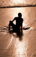 Man silhouetted at sunset at Seminyak Beach, Bali, Indonesia