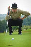 Golfer looks at putting on the green at Kendal golf club, Cumbria