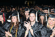 Jared Robert Fisher (Center) applaudes President McDavis's re,arkls during fall commencement. Photo by Ben Siegel