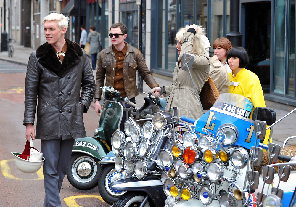 A group of mods, both men and women, with their scooters on a street in London, UK, 2010