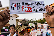 "12 JANUARY 2014 - BANGKOK, THAILAND: A woman holds up sign supporting Thai democracy during a candlelight vigil at Thammasat University in Bangkok. About 500 people from all walks of Thai life came to a candlelight vigil at Thammasat University. They prayed for a peaceful resolution to the political conflict in Thailand. They finished the vigil by singing the John Lennon song ""Imagine."" Anti-government protestors are expected ""Shutdown Bangkok"" Monday. There were reports Sunday evening that some intersections were already being blocked.       PHOTO BY JACK KURTZ"
