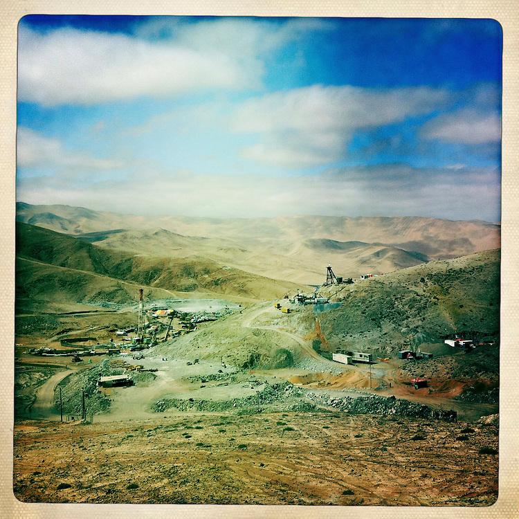 """Vista general de la Mina San jose, donde se lleban a cabo las operaciones de rescate de los 33 mineros atrapados a 700 metros de profundidad. Plan B, es un ensayo fotografico basado en aquellas cosas que la mirada somera no permite ver, de los días de espera, angustia, soledad y fe que las familias de los 33 hombres atrapados en la mina San Jose dejaron en el paisaje arido del desierto de Atacama tras el esperado rescate. """"Plan B"""", tambien es un acto de fe personal, por intentar plasmar en un relato diferente, sin más pretensión que la mirada interna a los sentimientos que esa montaña atrapó implacable y para siempre, pero que bajo la mirada superficial de los medios no permite escudriñar por tratarse de pequeños fragmentos que apelan a emociones individuales y no a la masividad que persiguen los reportes de prensa. Este ensayo es una invitación abierta a descubrir los pequeños milagros que florecieron en la montaña y en el día a día de cada una de las familias que nunca dejaron de creer en la vida, aun así se enfrentaran a la inmensidad del desierto y a las minimas espectativas de vida que el lugar entregaba.""""Plan B"""", esta constituido por fotografías ejecutadas en su totalidad con un telefono iPhone 4 y la aplicacion Hipstamatic. ROBERTO CANDIA / REVISTA NUESTRA MIRADA"""
