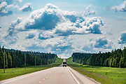 """Broad shoulders of the Alaska Highway, near Fort Nelson, British Columbia, Canada. The Alaska Highway was built as a military road during World War II in just 9 months in 1942, to link existing airfields via Canada to the territory of Alaska. The ALCAN Highway (a military acronym for Alaska-Canada) opened to the public in 1948. It begins in Dawson Creek, British Columbia, and runs via Whitehorse, Yukon to Delta Junction, Alaska. The """"Alaskan Highway"""" is comprised of British Columbia Highway 97, Yukon Highway 1 and Alaska Route 2. While the ALCAN measured 2700 kilometers (1700 mi) upon completion in 1942, by 2012 it was rerouted and shortened to 2232 km (1387 mi). Once legendary for being a rough, challenging drive, the highway is now paved over its entire length. Delta Junction, at the end of the highway, claims """"Historic Milepost 1422"""" where the Alaska Highway meets the Richardson Highway, which continues 96 mi (155 km) to the city of Fairbanks at Historic Milepost 1520, often (but unofficially) regarded as the northern portion of the Alaska Highway (although its Mileposts are measured from Valdez)."""