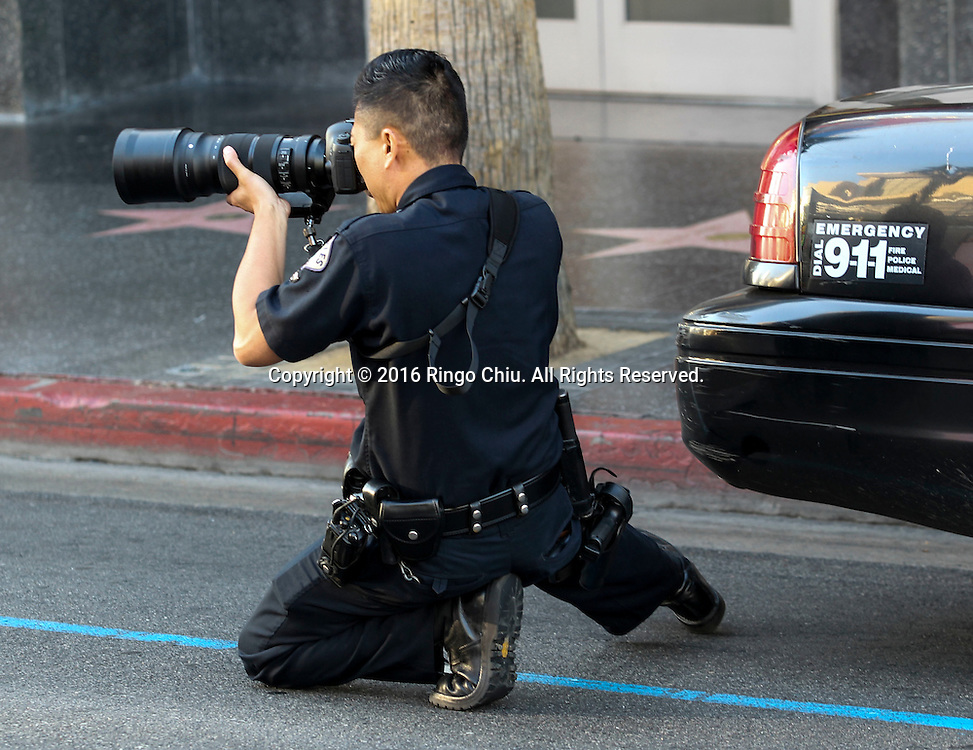 A police officer with a camera shooting along Hollywood Boulevard during the 31st Los Angeles Marathon in Los Angeles, Sunday, Feb. 14, 2016. The 26.2-mile marathon started at Dodger Stadium and finished at Santa Monica.  (Photo by Ringo Chiu/PHOTOFORMULA.com)<br /> <br /> Usage Notes: This content is intended for editorial use only. For other uses, additional clearances may be required.