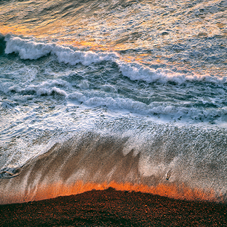 Breaking surf catches the late fiery light of sunset at Big Sur on the California coast.