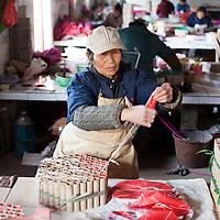 Hunan, Liuyang, Dec. 19..2013 : Xiao Shulan, a worker, assembles  fireckrackers for the Western market in a factory .