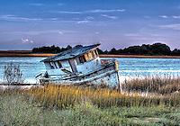 Fishing boat washed ashore on Intercoastal Waterway.