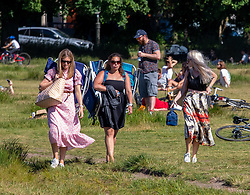 © Licensed to London News Pictures. 31/05/2020. London, UK. These three women carry sun loungers and picnic boxes as they head out in the sunshine on Wimbledon Common in South West London as weather experts predict another warm weekend with highs of 28c. On Monday, up to six people will be allowed to meet up in parks and private gardens. Photo credit: Alex Lentati/LNP