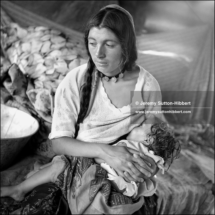 A mother breastfeeds her child inside the family tent,  in the Kalderash Roma camp of Sintesti, near Bucharest. August 1994