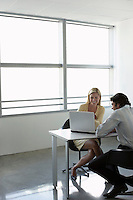 Business people using laptop sitting at office desk