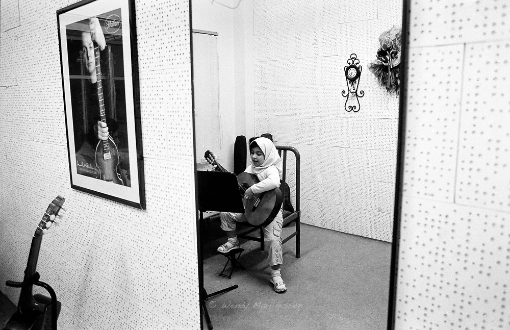 A little Iranian girl with headscarf during her guitar lesson. A poster of Paul McCartney hangs on the wall. Tehran, Iran, 2007