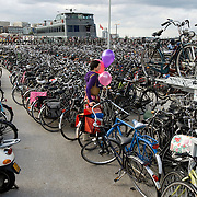 Nederland Amsterdam 6 september 2008 20080906 Foto: David Rozing .Vrouw parkeert haar fiets achter centraal station in fietsenstalling, op een drijvend ponton. Serie over Nederland in beweging .Woman is parking her bike on floating pontoon near the central ( train ) station. Also because of the small amount of space in this area the stabling is located on the water.  .cycling, bicycle, bicycles, lots of, huge amount, parking problems, typical dutch, ways of transport, going green, sustainable, leaving small footprint on earth, netherlands, known for, city of Amsterdam..Foto David Rozing