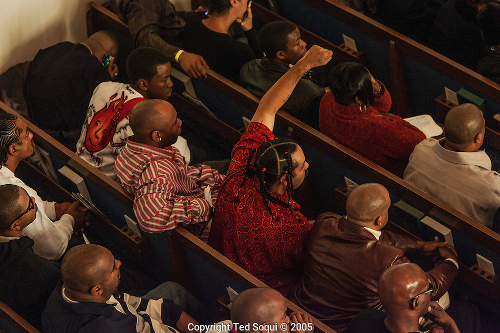 "People take cover as gangbangers shoot bullets into the air at the Funeral services for Stanley ""Tookie"" Williams at Bethel A.M.E. Church in S. Central LA. About 2000 people attended the services which included many gang members. The funeral was a star studded event attended by Jesse Jackson and rapper-actor Snoop Dogg, Nation of Islam leader Louis Farrakhan, and Bianca Jagger.  Loudspeakers and a large TV screen brought the service to many of the onlookers who could not get inside the packed church."