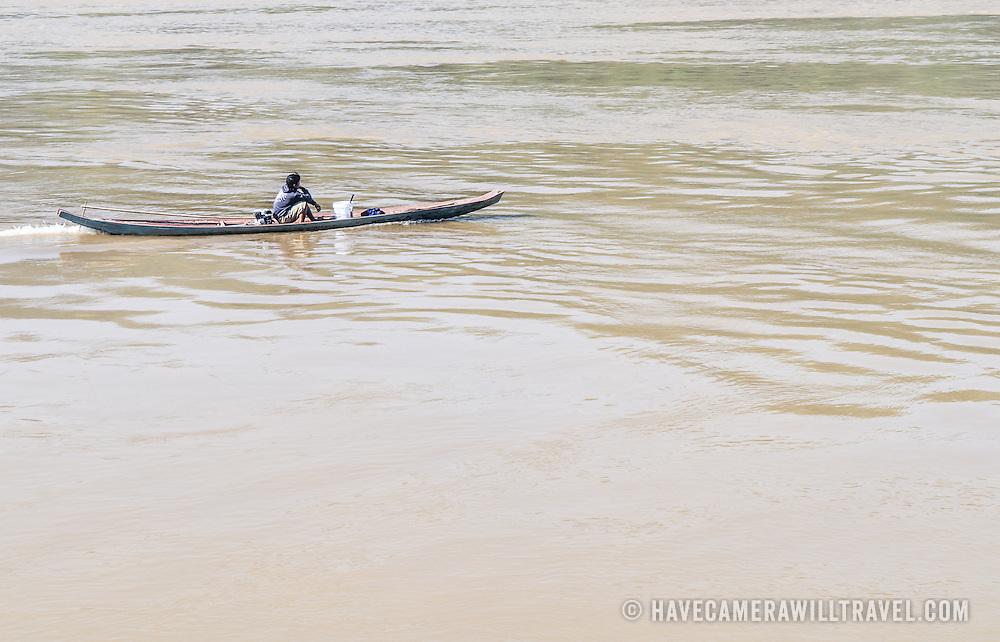 A young man motors his sampan along the  Mekong River near Luang Prabang in central Laos.