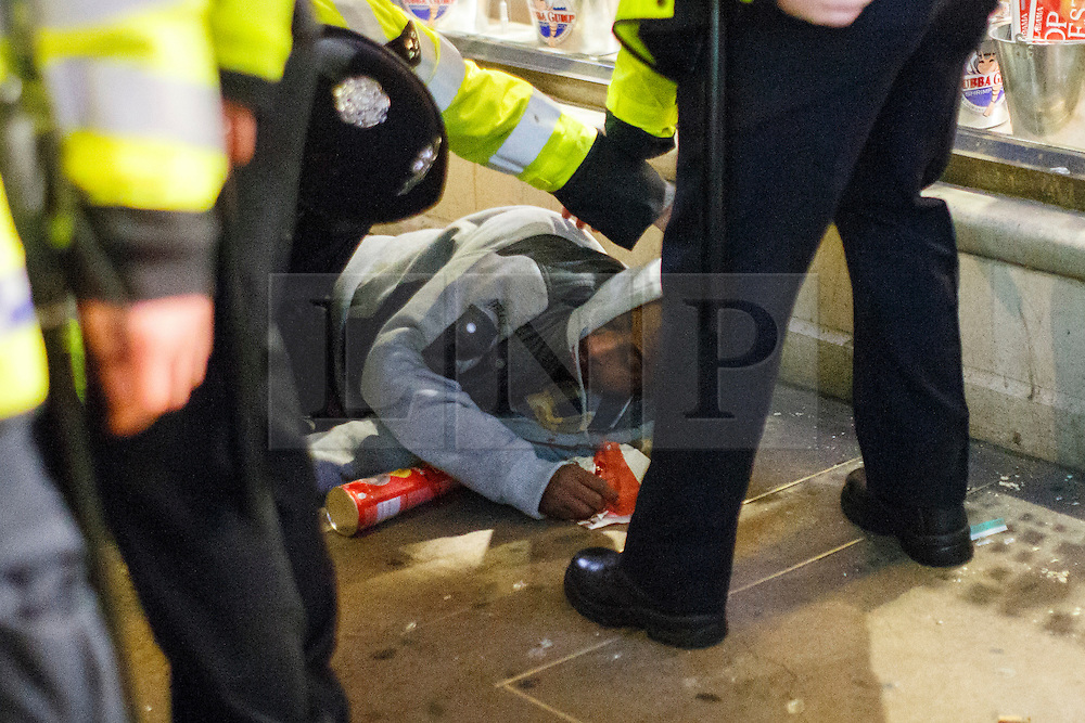 © Licensed to London News Pictures. 01/01/2016. London, UK. Police officers attending a man after an attack in central London at the first hours of 2016 on January 1, 2016. Photo credit: Tolga Akmen/LNP