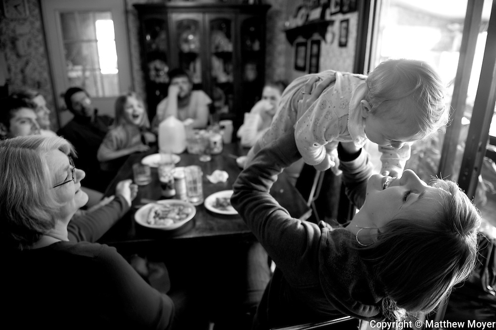 AUBURN, NEW YORK - MARCH 07: Meghan Nutting, right, plays with Leah Tidd, her soon-to-be niece, as the rest of the Tidd family looks on during a Sunday family dinner in Auburn, NY March 07, 2010. The Tidd family has been hit hard by the recent drop in milk prices. They recently had to get rid of their health insurance because it had gotten too expensive.