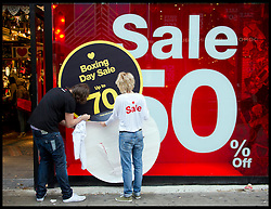 Staff at one store unveiling their Boxing Day 70% Sale on a busy Oxford Street in Central London as bargain hunters shop in the  Boxing Day Sales, Monday December 26, 2011. Photo By Andrew Parsons/i-Images