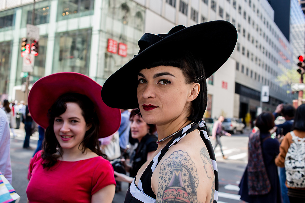 """New York, NY - April 16, 2017. A tattooed woman wears a jaunty black hat at New York's annual Easter Bonnet Parade and Festival on Fifth Avenue. The tattoo is of a perfume bottle labelled """"Oo-la-la."""""""