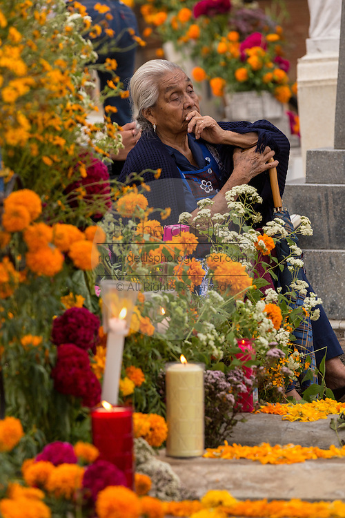 An elderly woman reflects at the gravesite of her deceased husband decorated at Xoxocatian cemetery decorated with flowers and candles for the Day of the Dead Festival known in spanish as Día de Muertos on October 31, 2014 in Oaxaca, Mexico.