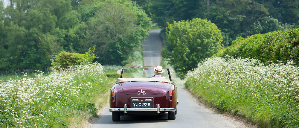 Motorist driving away in a British made Alvis TD21 classic car along a country lane in The Cotswolds, England