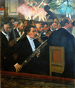 The Orchestra of the Opera', 1868-1869, oil on canvas. French artist Edgar Degas (1834-1917) a founder of Impressionism. Musicians in the orchestra pit playing for the Ballet, legs of and torsos of dancers in tutus on stage above them.  In centre foreground is the painter's friend the bassoonist Desire Dihau.