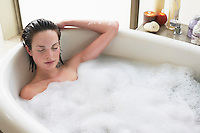 Young woman relaxing in bubble bath eyes closed. elevated view