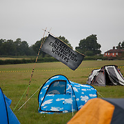 The farmer rentimng and running the field lives in the red house behind the camp.Reclaim the Power camp is set up in a field near Balcombe. The site is squatted but so far nor the owner nor police has made any moves to stop the camp from setting up. It is organised by the environmental group No Dash for Gas and the movement is protesting against the company Cuadrilla's fracking testing near Balcombe and have come to Balcombe to len its support to the local protests against the drilling for gas.