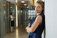 Woman leaning against wall in office corridor portrait