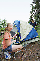 Two teenage girls setting up tent on camp site, portrait