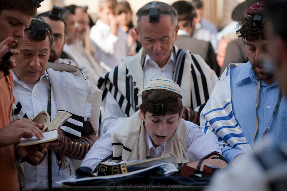 A boy reads a religious scripture at the Western Wall, in the Old City, Jerusalem, Israel.