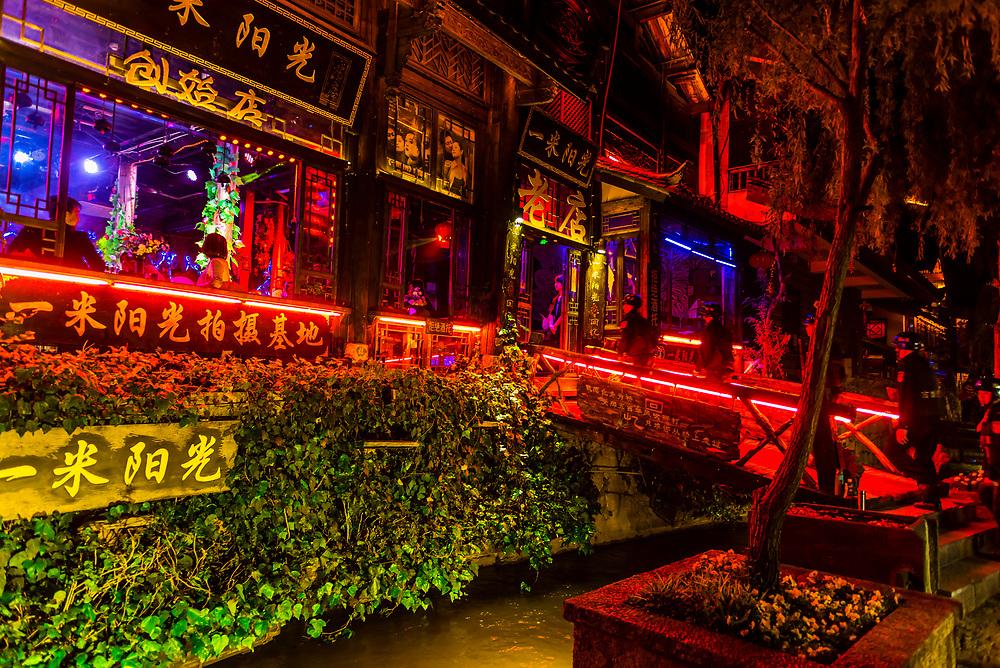 Colorful lights illuminate bars and restauants along Bar Street (Xinhua Street) in the Old Town (Dayan) ofLijiang, Yunnan Province, China.