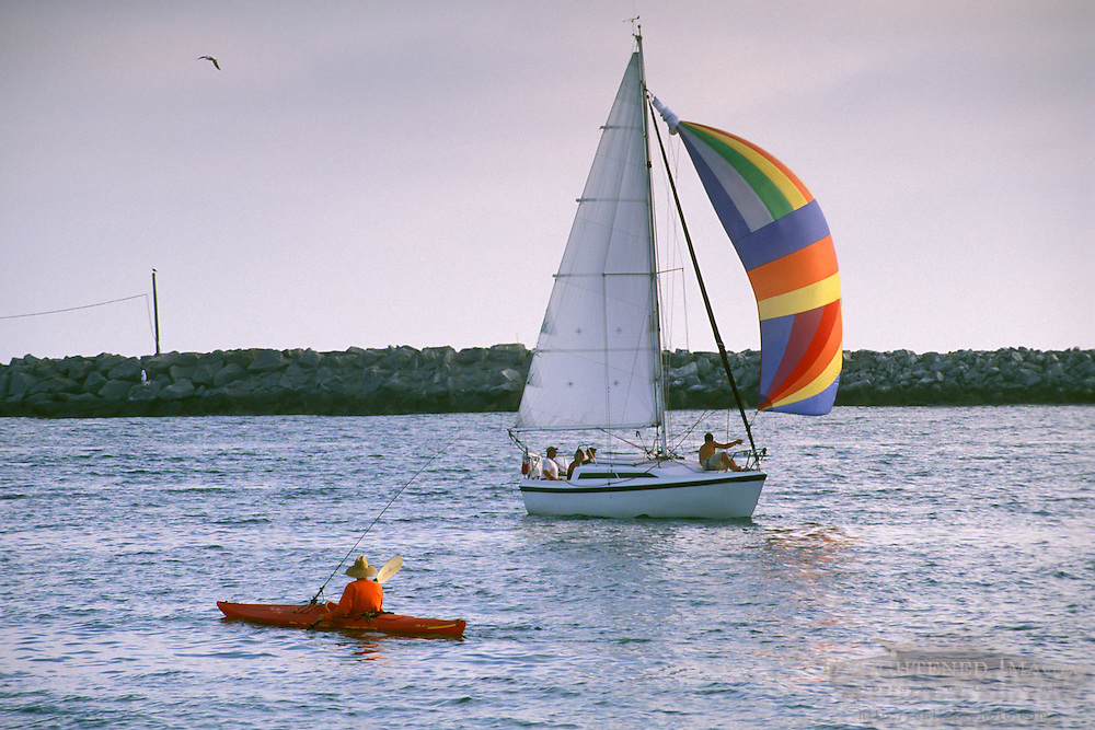 Sailboat passing Lone male adult person fishing from kayak in harbor channel, Newport Beach, Orange County, California