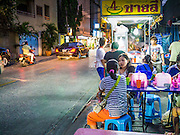 """30 MARCH 2013 - BANGKOK, THAILAND:  People at a street food stall in Bangkok. Thailand's economic expansion since the 1970 has dramatically reduced both the amount of poverty and the severity of poverty in Thailand. At the same time, the gap between the very rich in Thailand and the very poor has grown so that income disparity is greater now than it was in 1970. Thailand scores .42 on the """"Ginni Index"""" which measures income disparity on a scale of 0 (perfect income equality) to 1 (absolute inequality in which one person owns everything). Sweden has the best Ginni score (.23), Thailand's score is slightly better than the US score of .45.  PHOTO BY JACK KURTZ"""