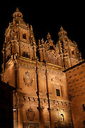 """Low angle view of Clerecia Church,  Salamanca, Spain, pictured on December 19, 2010 at night floodlit. The wall of the Casa de las Conchas iis visble on the right. The Baroque style Clerecia Church, originally the Royal College of the Company of Jesus, was commissioned in the 17th century, from architect Juan Gomez de Mora, by Queen Margarita of Austria, wife of Philip III of Spain. It comprises two sections: the Jesuit school and church, with its three-storey Baroque cloister, and private living quarters for the monks and now houses the Salamanca Pontificia University. Salamanca, an important Spanish University city, is known as La Ciudad Dorada (""""The golden city"""") because of the unique golden colour of its Renaissance sandstone buildings. Founded in 1218 its University is still one of the most important in Spain. Around it the Old Town is a UNESCO World Heritage Site. Picture by Manuel Cohen"""