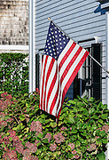 American flag hangs on New England house.