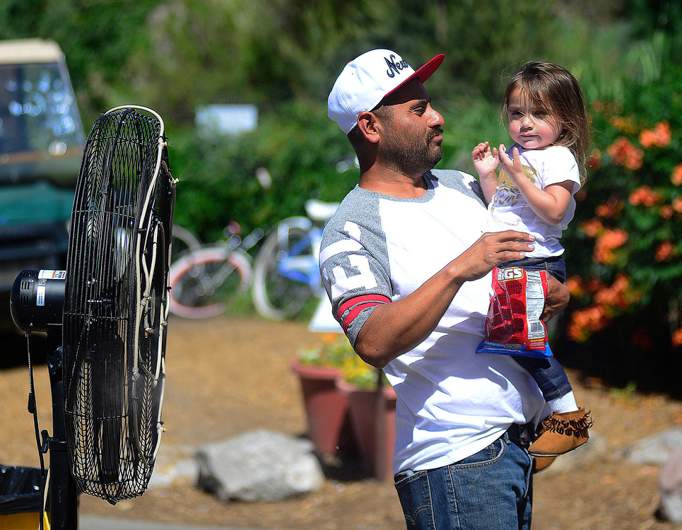 apl061817b/ASECTION /pierre-louis/JOURNAL 061817<br /> Jorge Cardenas,, holds his 2 year-old daughter Jaqueline Cardenas,, in front of a mist fan to try to cool off during  Father's Day at the Zoo .Photographed  on Sunday June  18,  2017. .Adolphe Pierre-Louis/JOURNAL