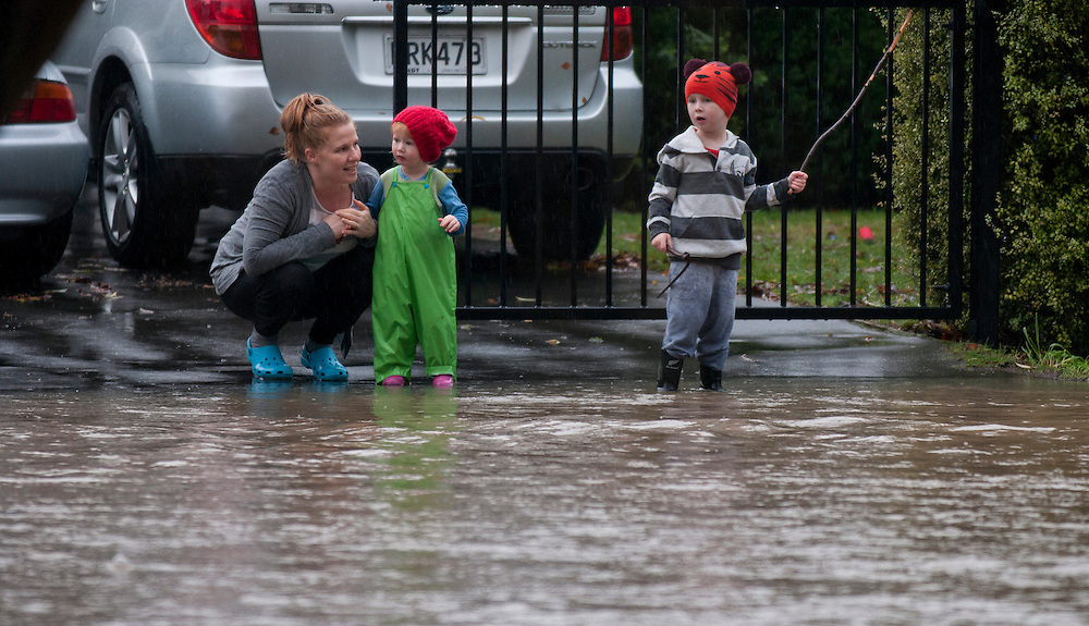 A Family watches from their gate flooding along EasternTerrace from the Heathcote River, Christchurch, New Zealand, Monday June 17, 2013. Credit:  SNPA / David Alexander