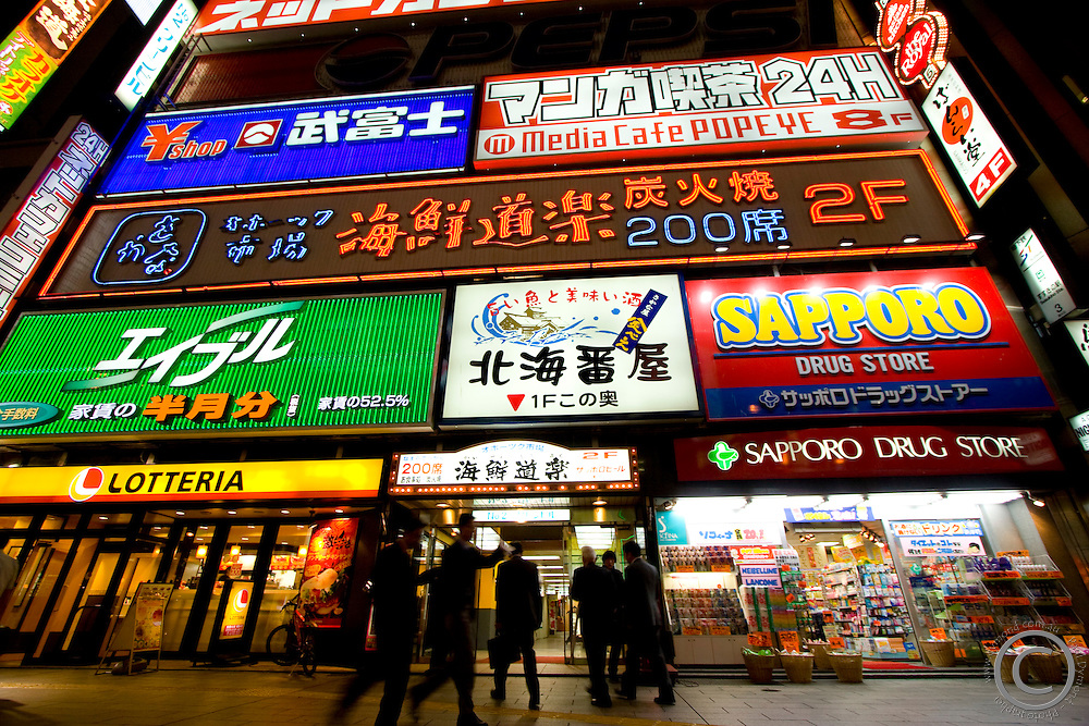 Businessman congregate under a giant wall of neon signs in the entertainment district of Sapporo - known as Susukino. Hokkaido, Japan