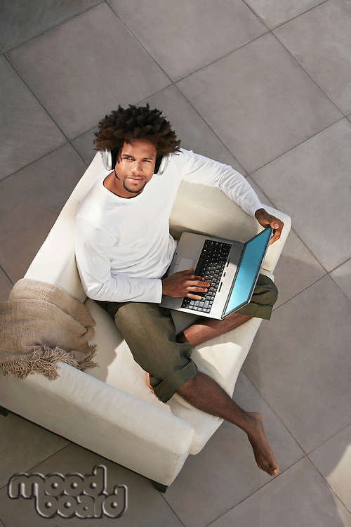 Young man sitting on sofa outside using laptop and listening to music through earphones portrait overhead view