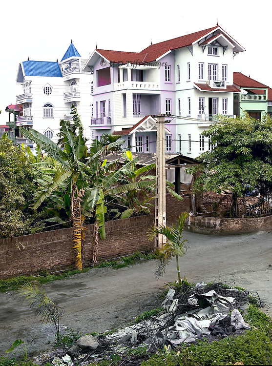 Hanoi suburbs:  new house and apartment buildings follow traditional urban style of architecture, a tall and narrow 4-5 floor structure one or two rooms wide.  Uncollected trash in the street.