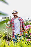 Portrait of mature man holding fork rake in garden shop