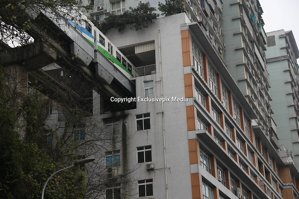 CHONGQING, CHINA - <br /> <br /> Light Railway Passes Through Residential Building<br /> <br />  A light railway train passes through a residential building in Chongqing, China. Chongqing Rail Transit No.2 and a 19-storey residential building have been built across each other. The railway set its Liziba Station on the sixth to eighth floor in the building with noise reduction equipment. ©Exclusivepix Media